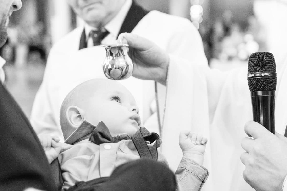 Ksiądz polewający główkę dziecka w Kościele podczas chrztu świętego