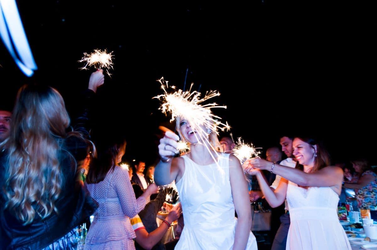 Państwo Młodzi oraz goście trzymający zimne ognie podczas wesela